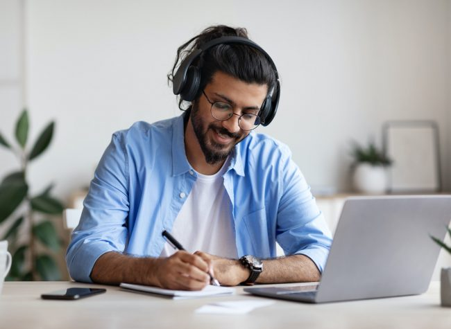 Western Guy Wearing Headphones Studying Online With Laptop At Home, Taking Notes